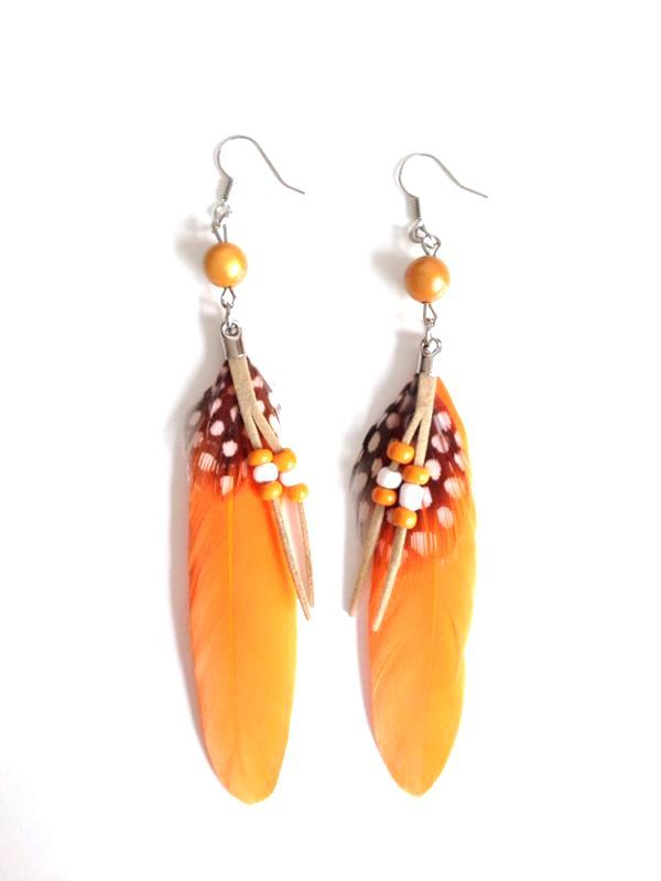 Prachtige opvallende oorbellen met echte veren hangend onder een opvallende kraal in dezelfde kleurstelling. Op de lange veer een klein gestippeld veertje en subtiel suede vetertje met kraaltjes. Lengte ca. 11,5 cm. Kleur oranje. Zie afbeelding.