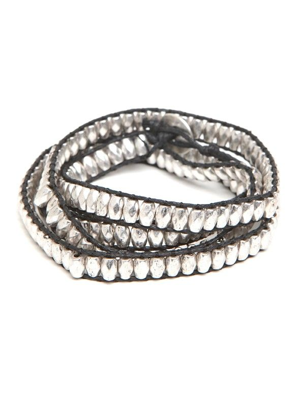 The mix of sleek metal beads and tough leather accents keep this streamlined wrap bracelet looking sleek and versatile.  A long row of elongated silver-tone beads are strung on thin black leather cord.  A single silver-tone button sits on one end of the bracelet and two different openings on the other end of the bracelet allow for sizing options.