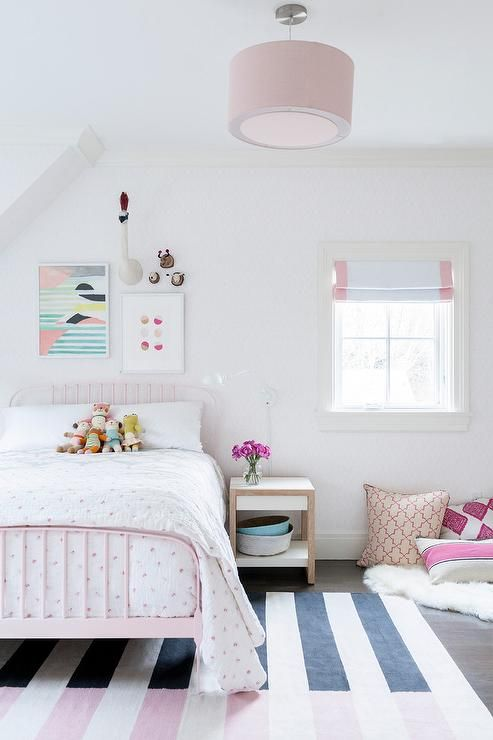 A Pink Drum Pendant Light Hangs Over A Pink And Black Striped Rug