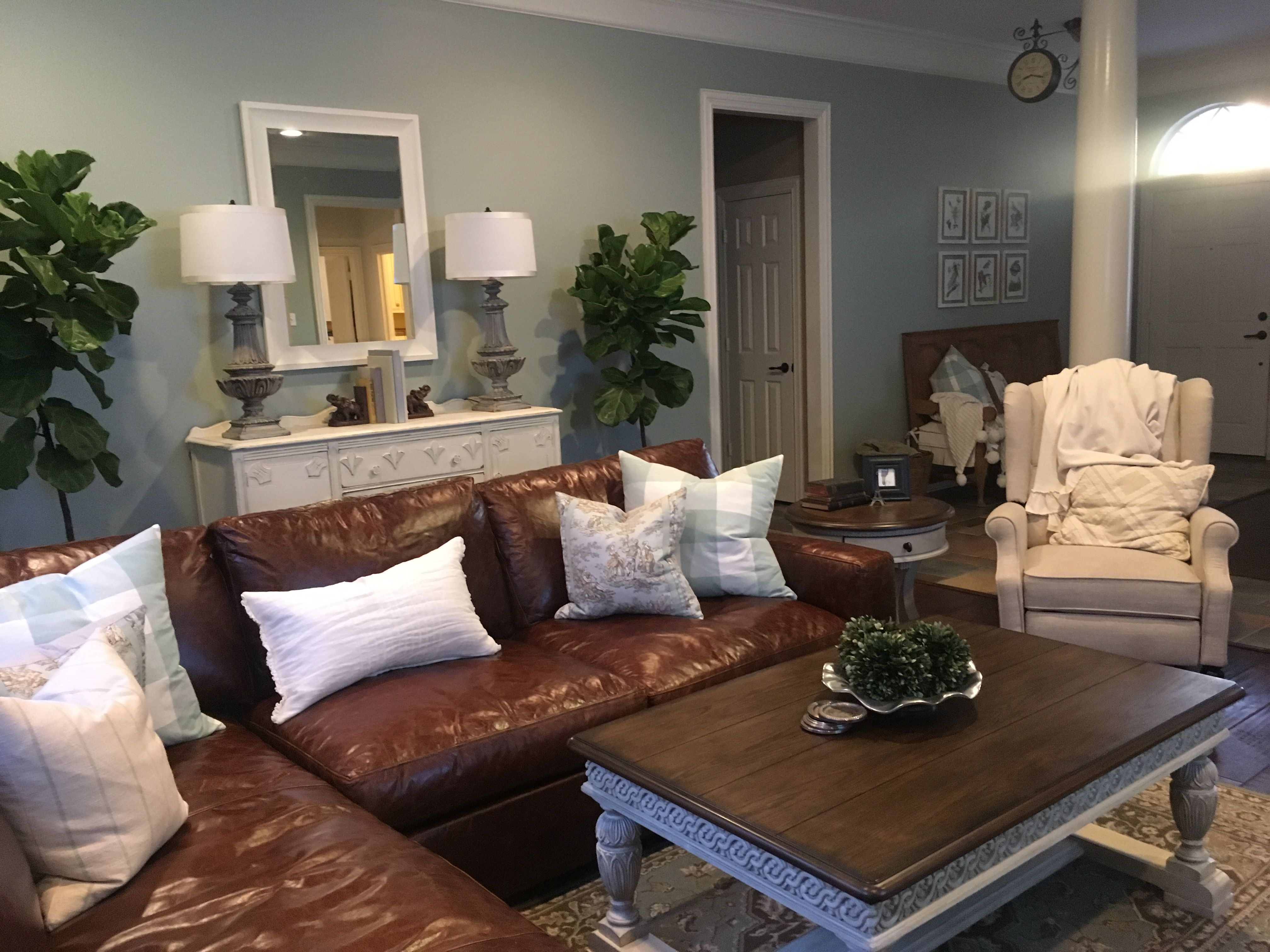 French Country living room after makeover in a Southern Texas Home. Leather couch buffalo check walls Sherwin Williams 75% done by Bluebonnet Home. Vintage Buffet chalk painted cream. After picture.