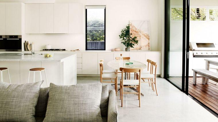 ambiente unico con cucina con mobili bianchi, tavolo ovale ...