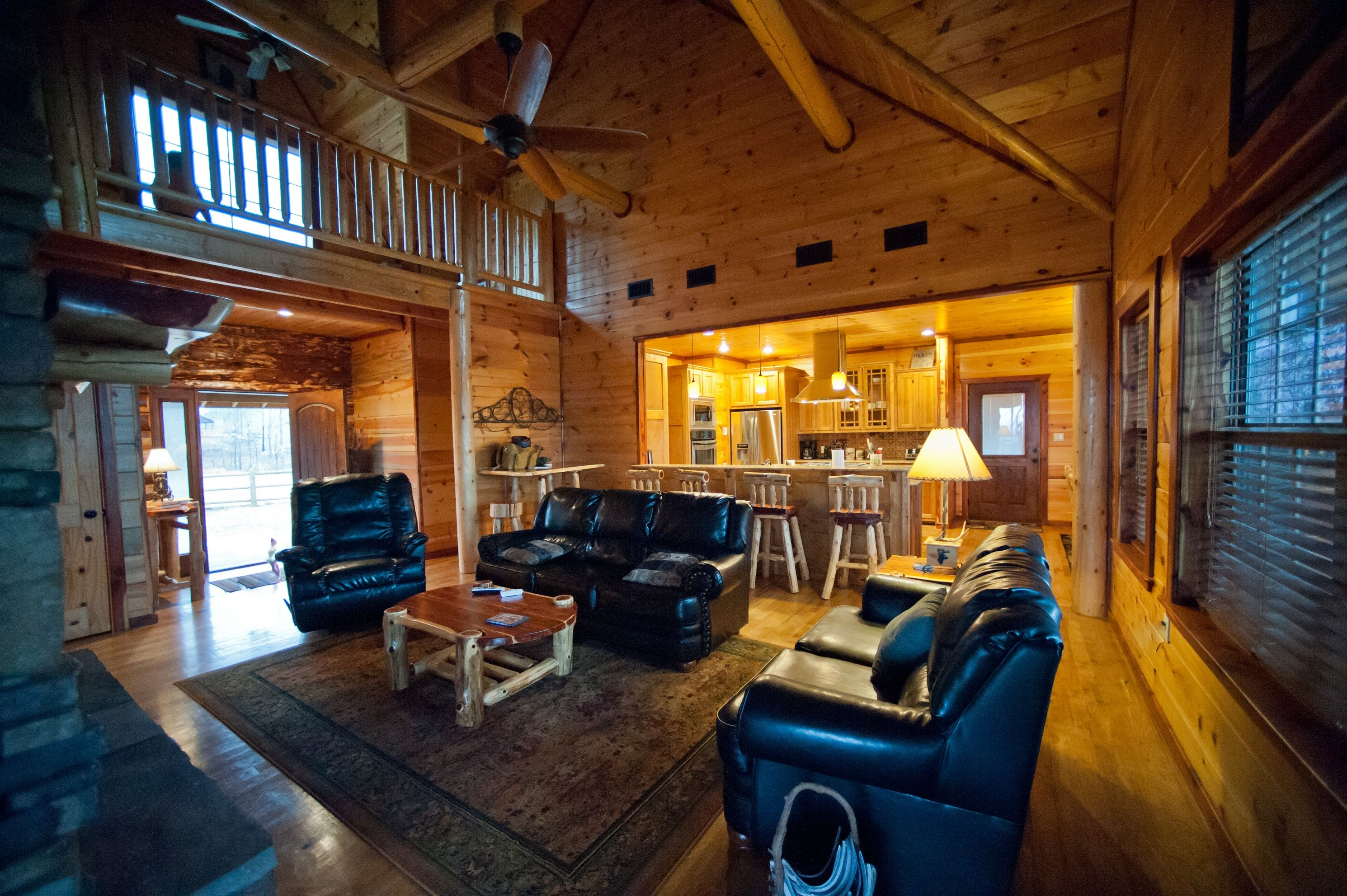 View of the living room and kitchen on the main level of The Lake House Cabin at Broken Bow.