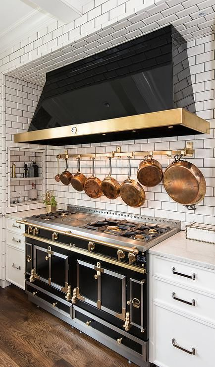 A Subway Tiled Cooking Nook Is Filled With A Black Kitchen