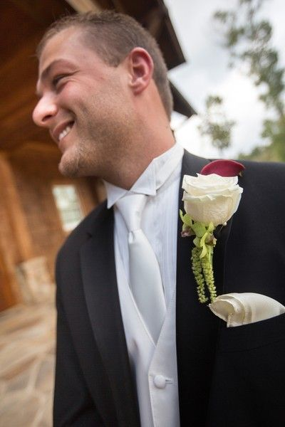 """<strong class='info-row'>Mike Moon Studio</strong> <div class='info-row description'><html>  <head></head>  <body>    Nate looked dapper in a black suit accessorized with a white necktie and rose boutonniere attached to his lapel.  Venue:   <a href=""""http://www.weddingwire.com/reviews/foxhall-resort-and-sporting-club-douglasville/c027df18727969e8.html"""" target=""""_blank"""">Foxhall Resort and Sporting Club</a>   </body> </html></div>"""