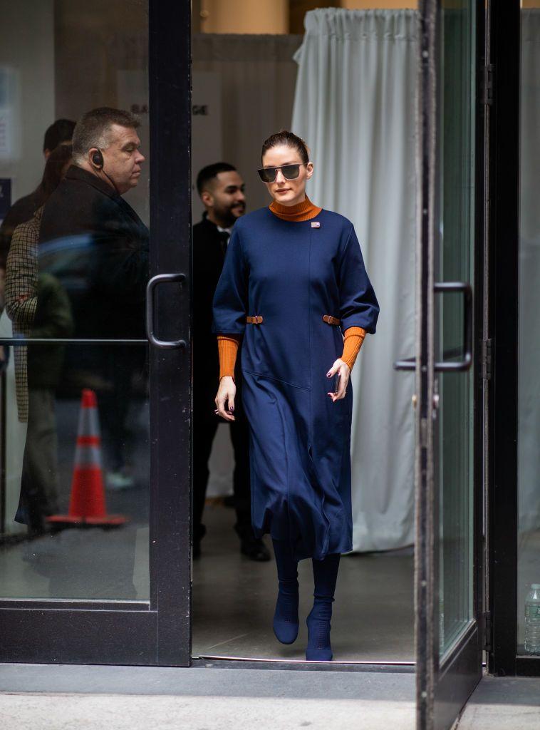 Olivia Palermo is seen wearing orange jumper, navy dress