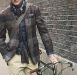 Plaid coat over a dark denim collar shirt with a tucked in scarf