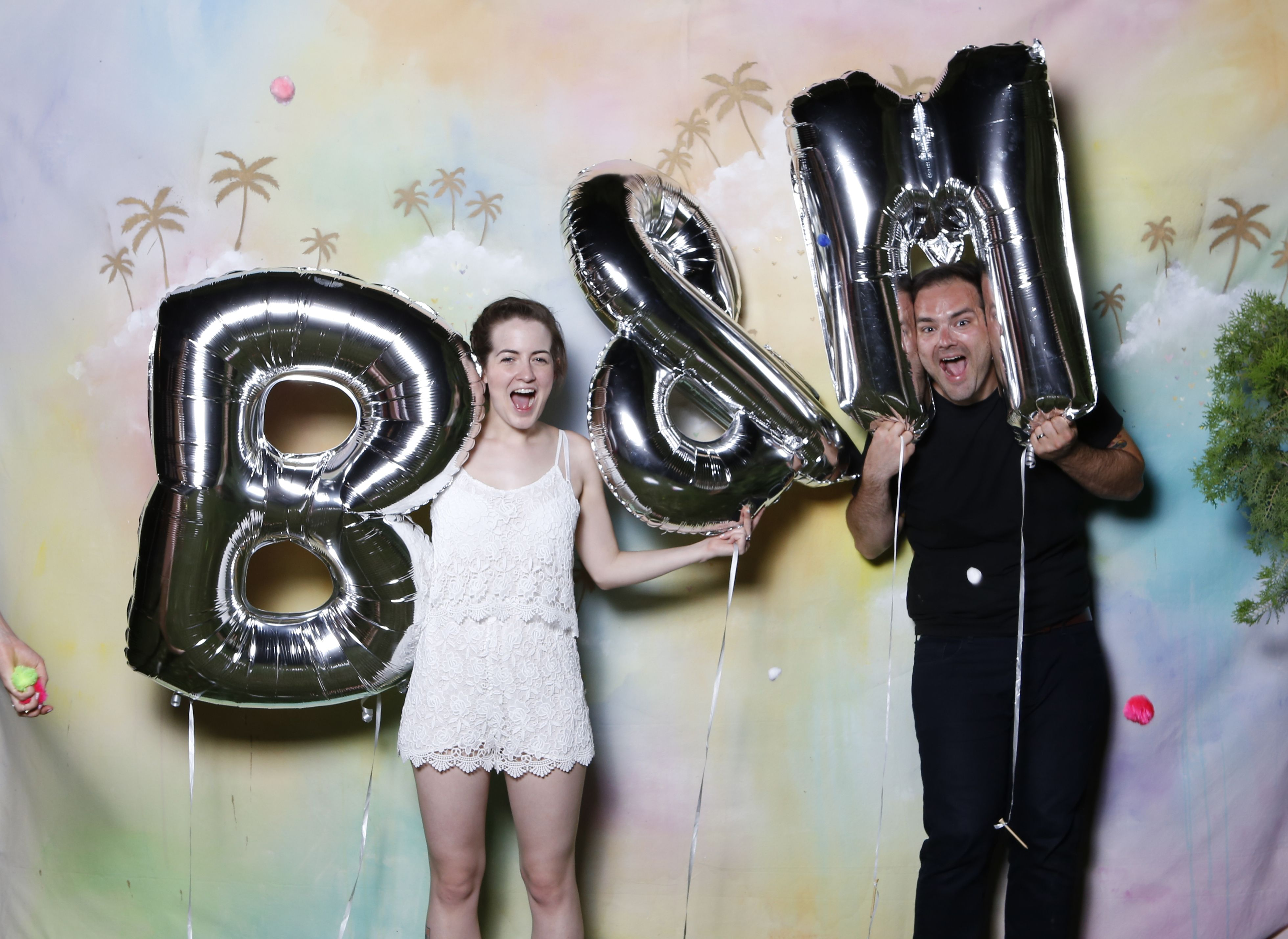 Handpainted Photobooth Backdrop by Melissa Wickham, Silver Letter Balloons, pom poms, palm trees.