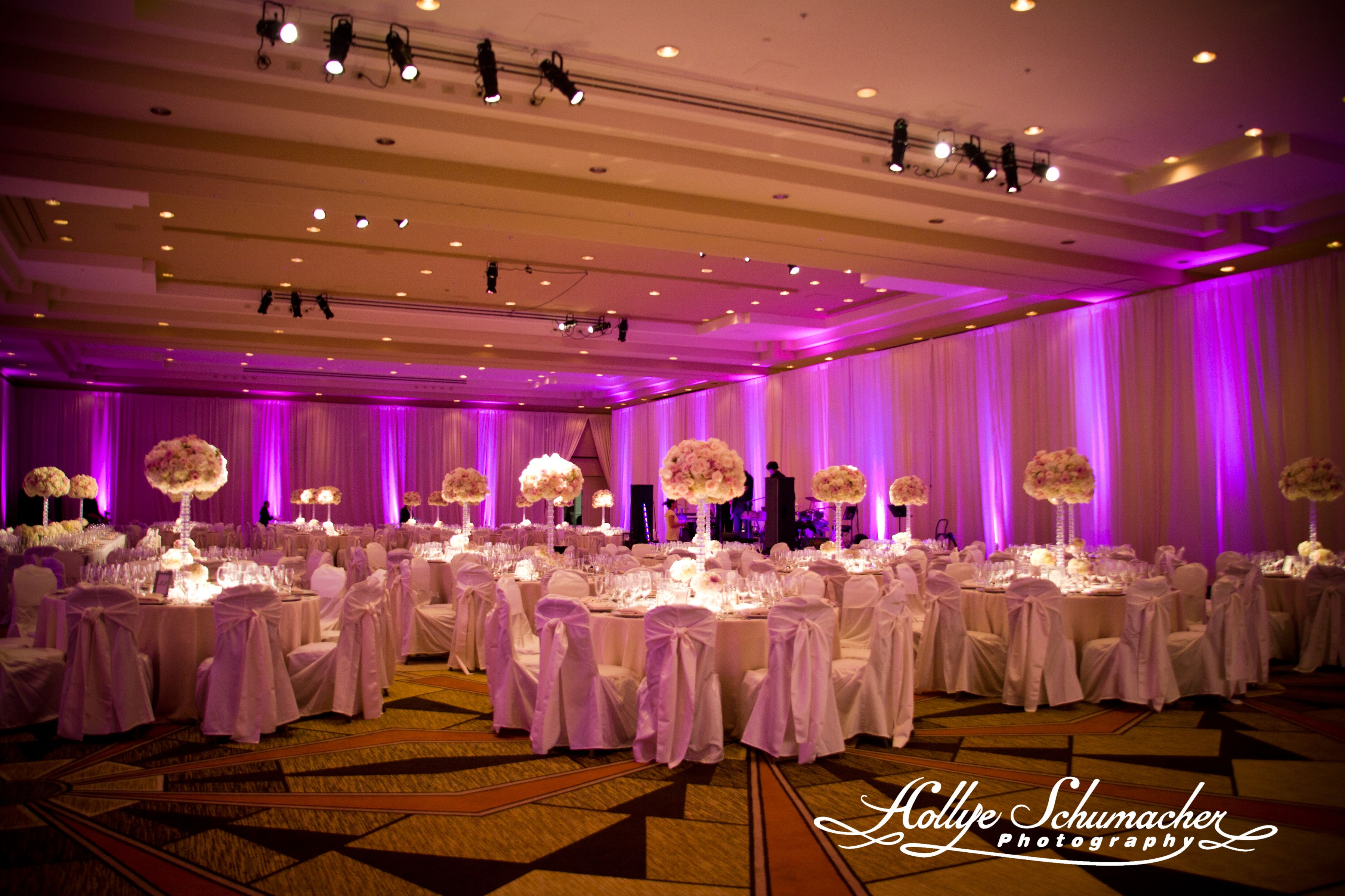 Stunning ballroom with pink up-lights and tall floral centerpieces ...
