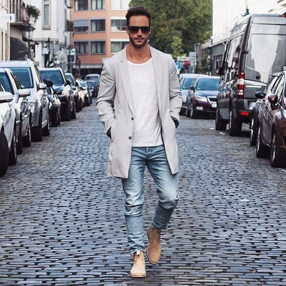 Dress in a grey trench and light blue jeans for your nine-to-five. Take a classic approach with the footwear and go for a pair of camel suede chelsea boots. Shop this look on Lookastic: https://lookastic.com/men/looks/trenchcoat-crew-neck-t-shirt-jeans/18415 — Dark Brown Sunglasses — White Crew-neck T-shirt — Grey Trenchcoat — Light Blue Jeans — Tan Suede Chelsea Boots