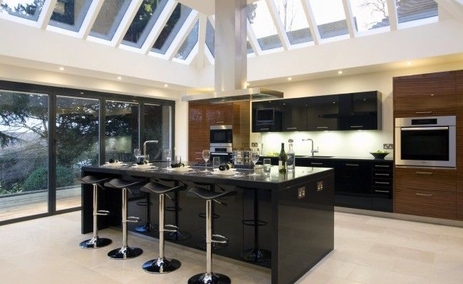 high gloss black and timber kitchen under a large glass