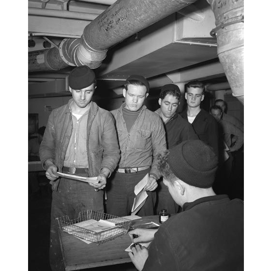 Sailors line up to send off their Mother's Day V-Mail letters, keeping in touch on their mothers' and/or wives' special day. The men in line do not look happy, assuming it is because they cannot spend the day with their family, but the V-Mail allows them to show that they care even though they are far away.