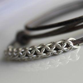 Rund åpen brynje av 0,9mm sølvtråd, tredd på snorer av skinn. Snorene kan justeres til ønsket lengde.