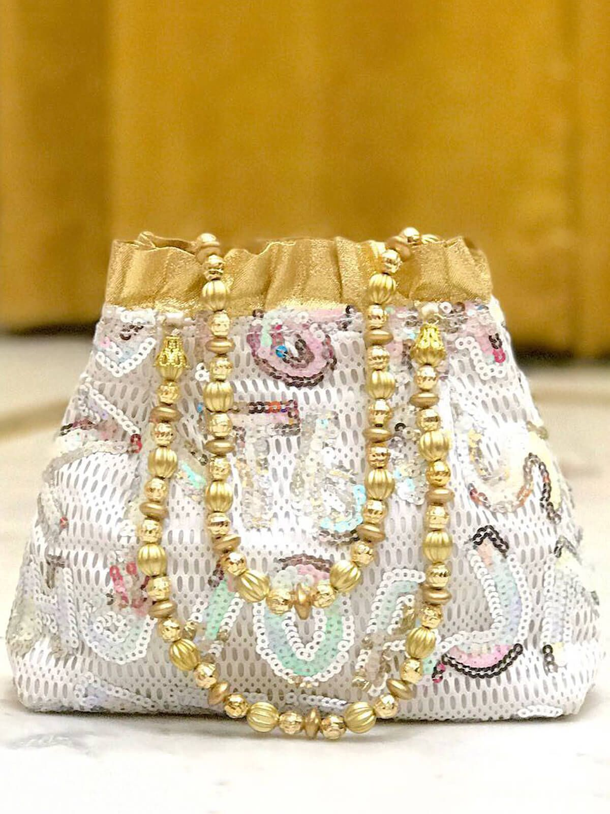a9f027dcb34 Distinguished white and golden festival wear lace potli bag. Having  material lace. Featured with