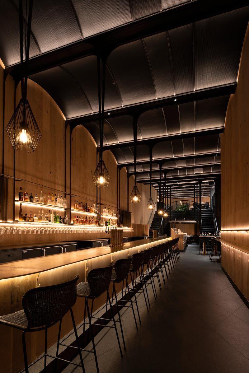 Restaurant Lighting This Modern Restaurant Has A High Vaulted Ceiling Wood Walls Hidden Lighting An Ex In 2020 Modern Restaurant Hidden Lighting Restaurant Lighting
