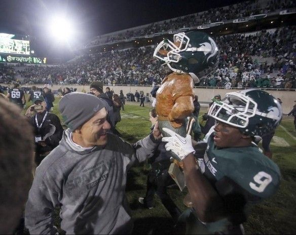 Julian H. Gonzalez/DFP Michigan State head coach Mark Dantonio reaches out to touch the Paul Bunyan trophy as Isaiah Lewis carries it bay and to the locker room after MSU's 29-6 win over Michigan in East Lansing on Saturday, November 2, 2013.