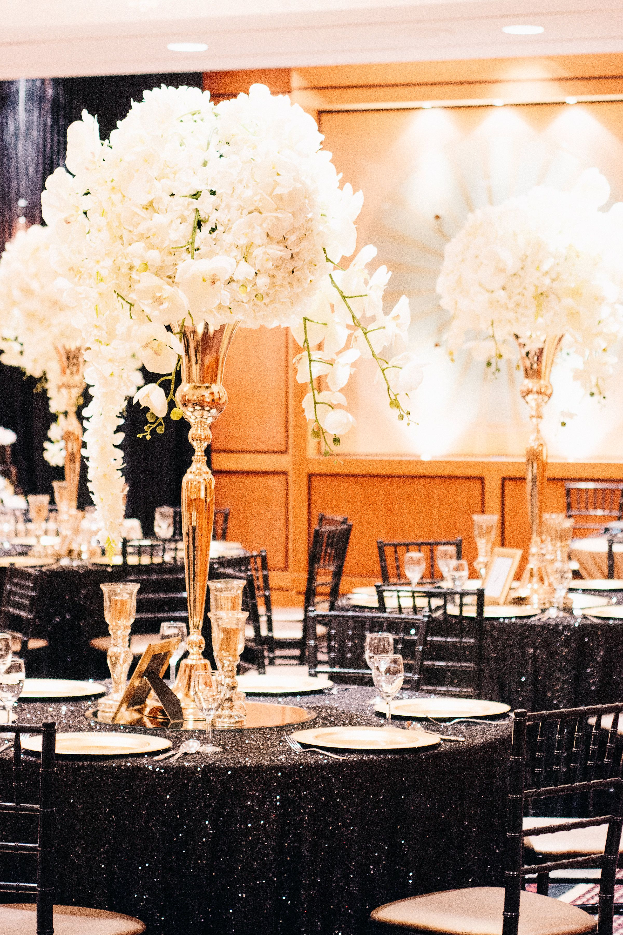 Beautiful large all white floral. Black and gold theme wedding. Elegant and  classy.   Black and gold theme, Gold wedding theme, Corporate events  decoration