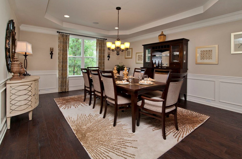 Dining room with dark wood floors and tray ceilings.