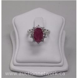 Ladies 18kt White gold diamond and ruby ring. It contains 1 oval cut ruby (4.80ct) and 10 round bril - Auction Network