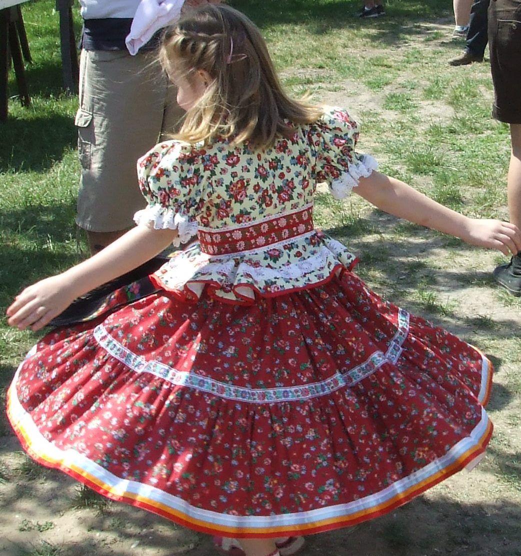 a happy liitle girl in a Matyó folk dress