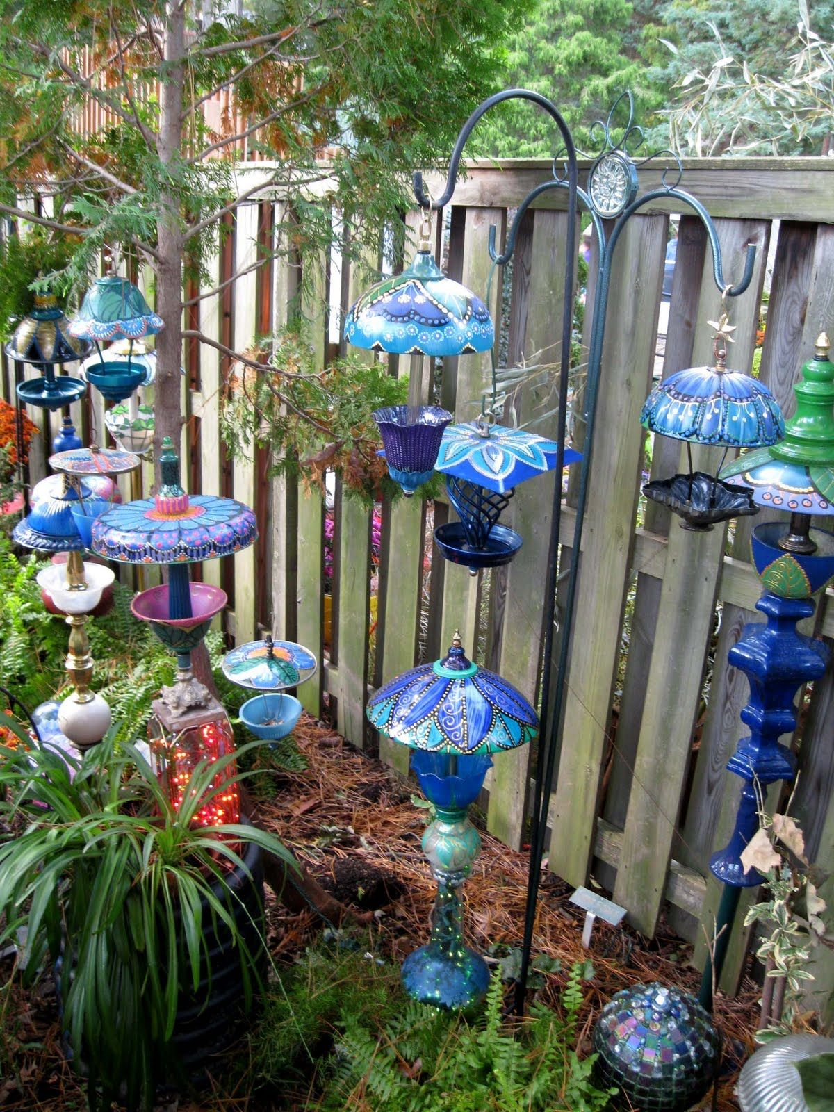 Whimsical garden lamps and bird feedersLove these  Garden art