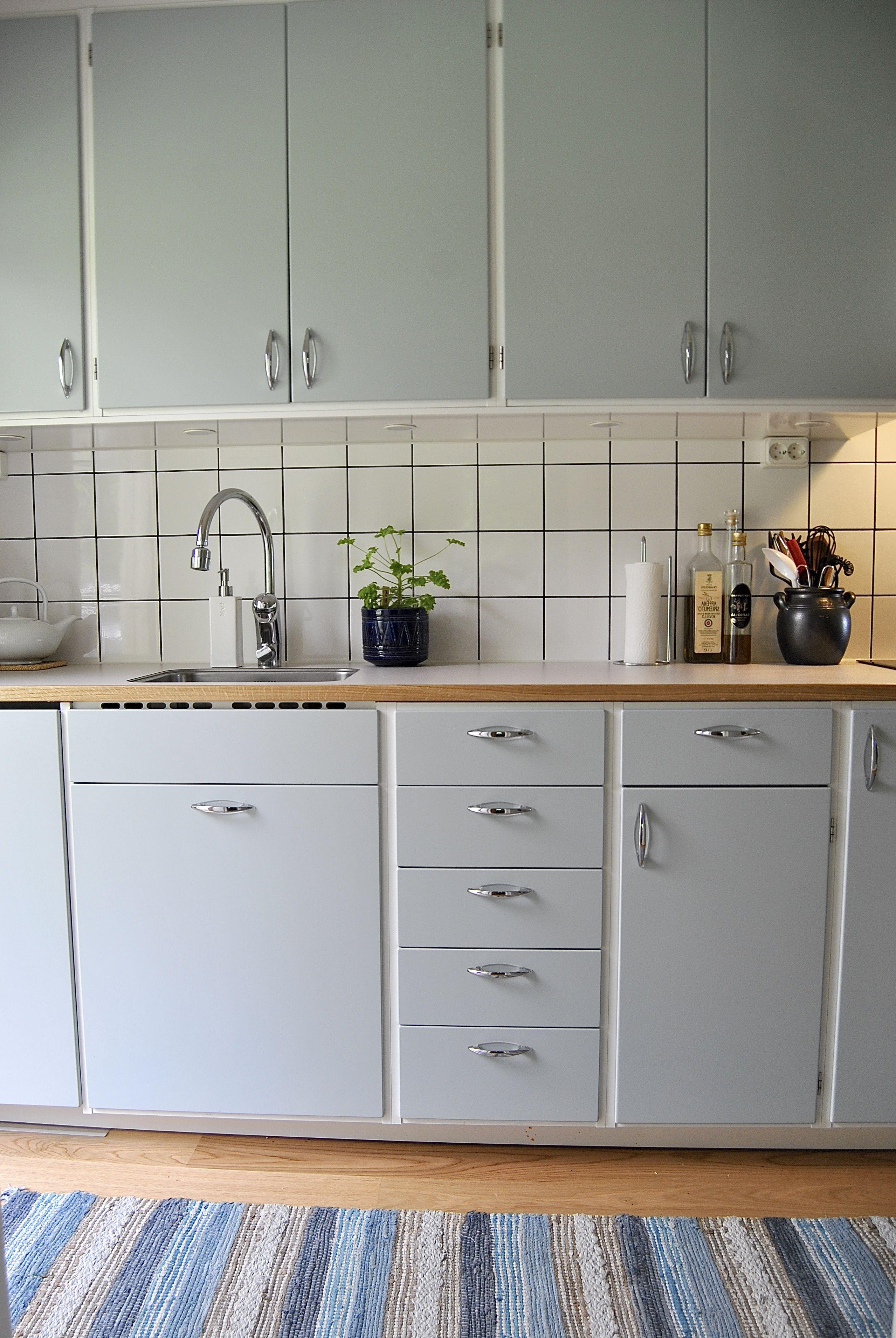 1960 tals kök med falsade luckor i mild gråblå färg. Kakel i