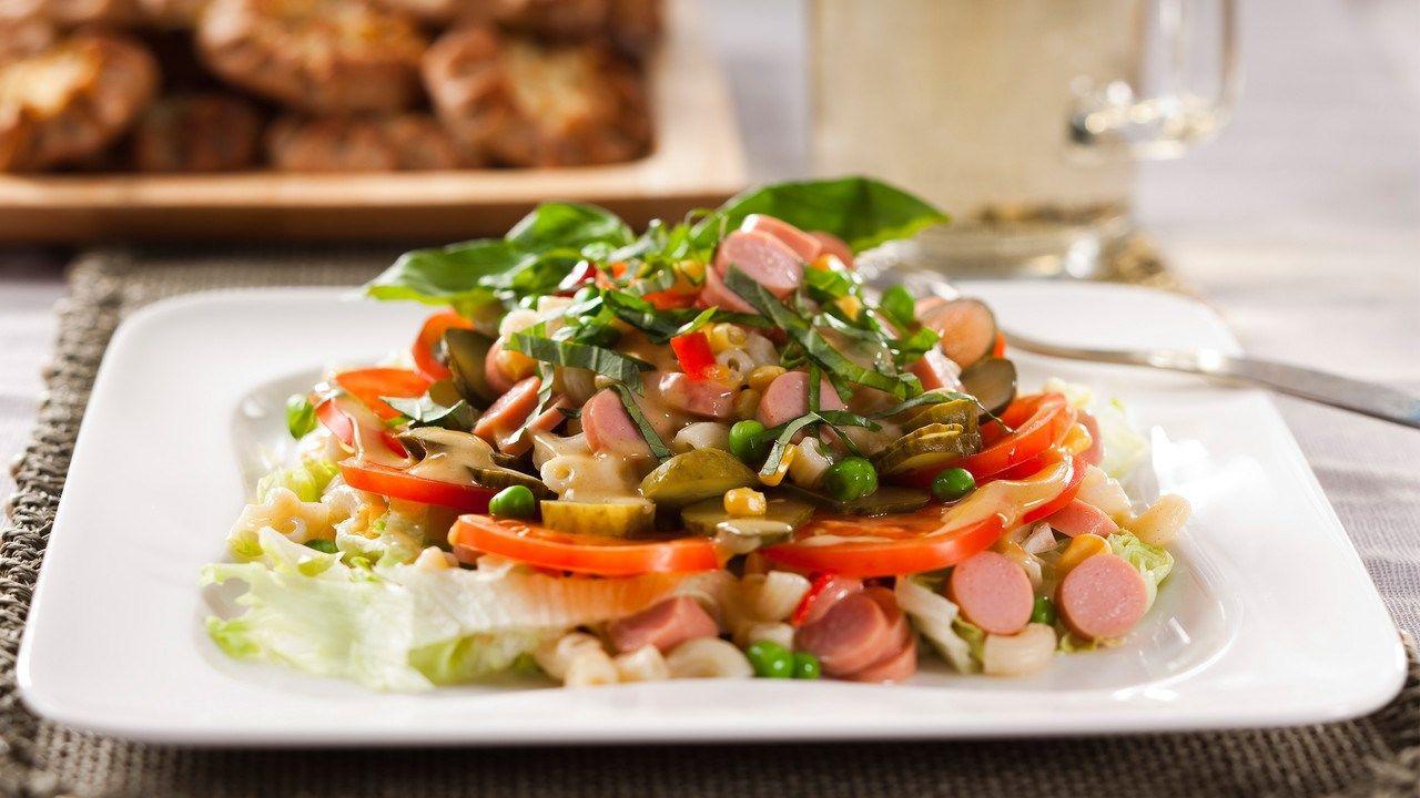 Keitä makaronit suolalla maustetussa vedessä kypsiksi. Huuhtele ne kylmällä vedellä ja valuta hyvin siivilässä. Kaada keitetyt makaronit kulhon pohjalle ja kaada päälle osa sinappikastikkeesta. Anna maustua. Viipaloi nakit. Suikaloi salaatti ja viipaloi maustekurkku sekä tomaatit. Lado ainekset kerroksittain kulhoon ja kostuta lopulla sinappikastikkeella. Hienonna pinnalle tuoreita yrttejä. Anna maustua kylmässä ennen tarjoilua. Valmista sinappikastike. Sekoita sinappi, mausteet ja…