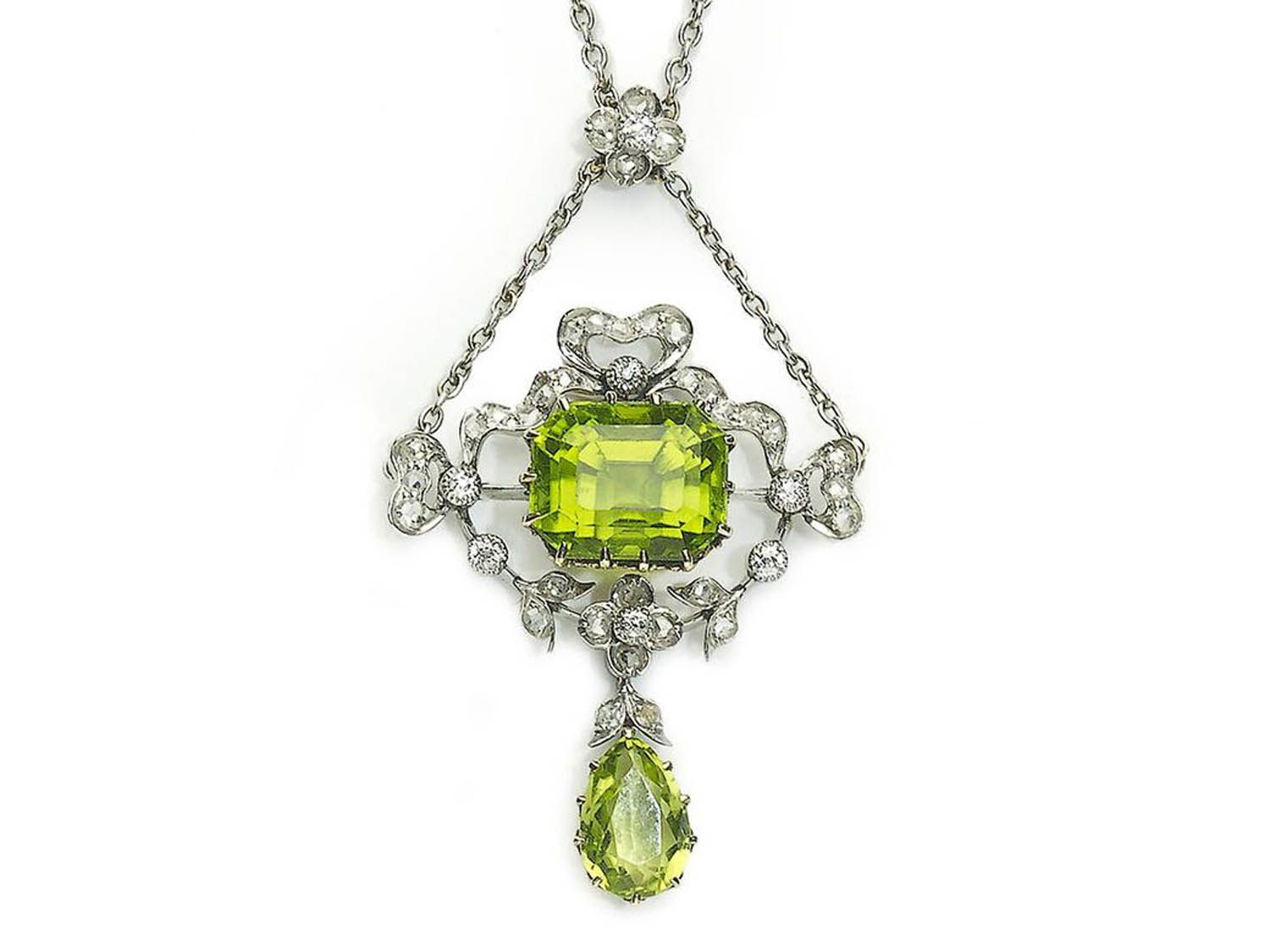 An edwardian peridot pendant set with an emeraldcut and a pear