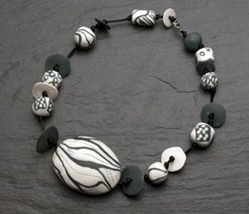 """Necklace in slate and white porcelain, satin cord, and sterling silver clasp. Necklace is 26"""" in length. Center bead measures 3 x 2.5 x 1"""""""