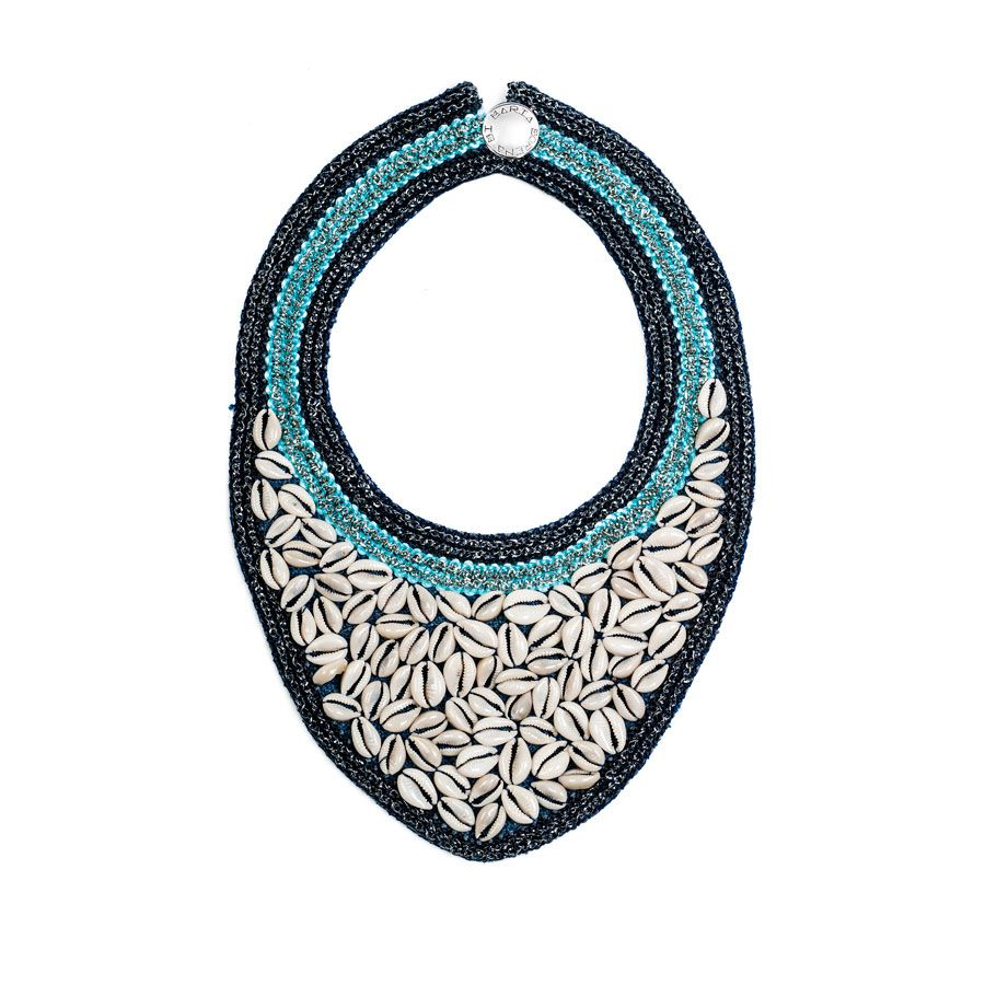 Collar de inspiración tribal con pasamanería metálica sobre yute entrelazadas con conchas auténticas de Kenia. De un colorido espectacular azul marino y turquesaque hace resaltar la elegancia y exclusividad del complemento.
