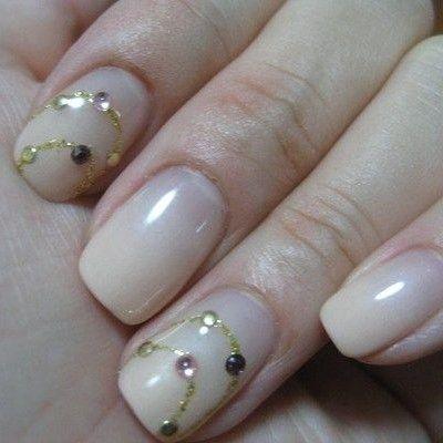 Preciosas uñas en color beige, decoradas en algunas con líneas onduladas doradas y perlas negras, rosas y doradas.