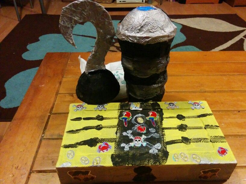 DIY Pirate accessories  Treasure chest - cardboard box, painted and decorates  Hook - yogurt pot and cardboard taped  together, covered in paper and painted  Telescope - Ice cream pots tapped together and covered in paper machete. Painted and decorate. String added to wear around neck