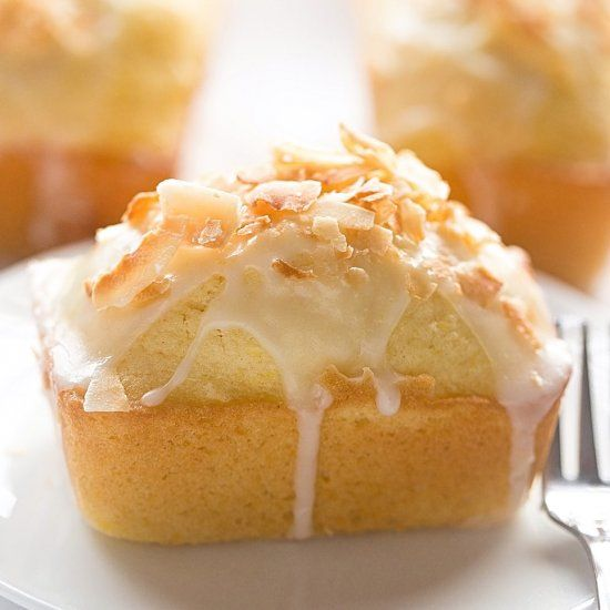 Mini Lemon Coconut Loaf Cakes: easy, soft, fluffy, loaf cakes full of lemon flavor and coconut flakes with a glossy, tangy glaze.
