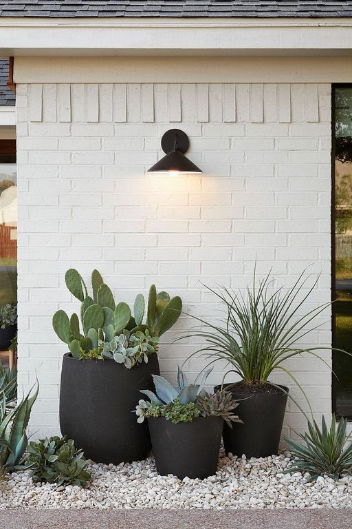 Photo of minimalist outdoor decor; black planters with succulents; industrial lighting #midcentury #modern #m…