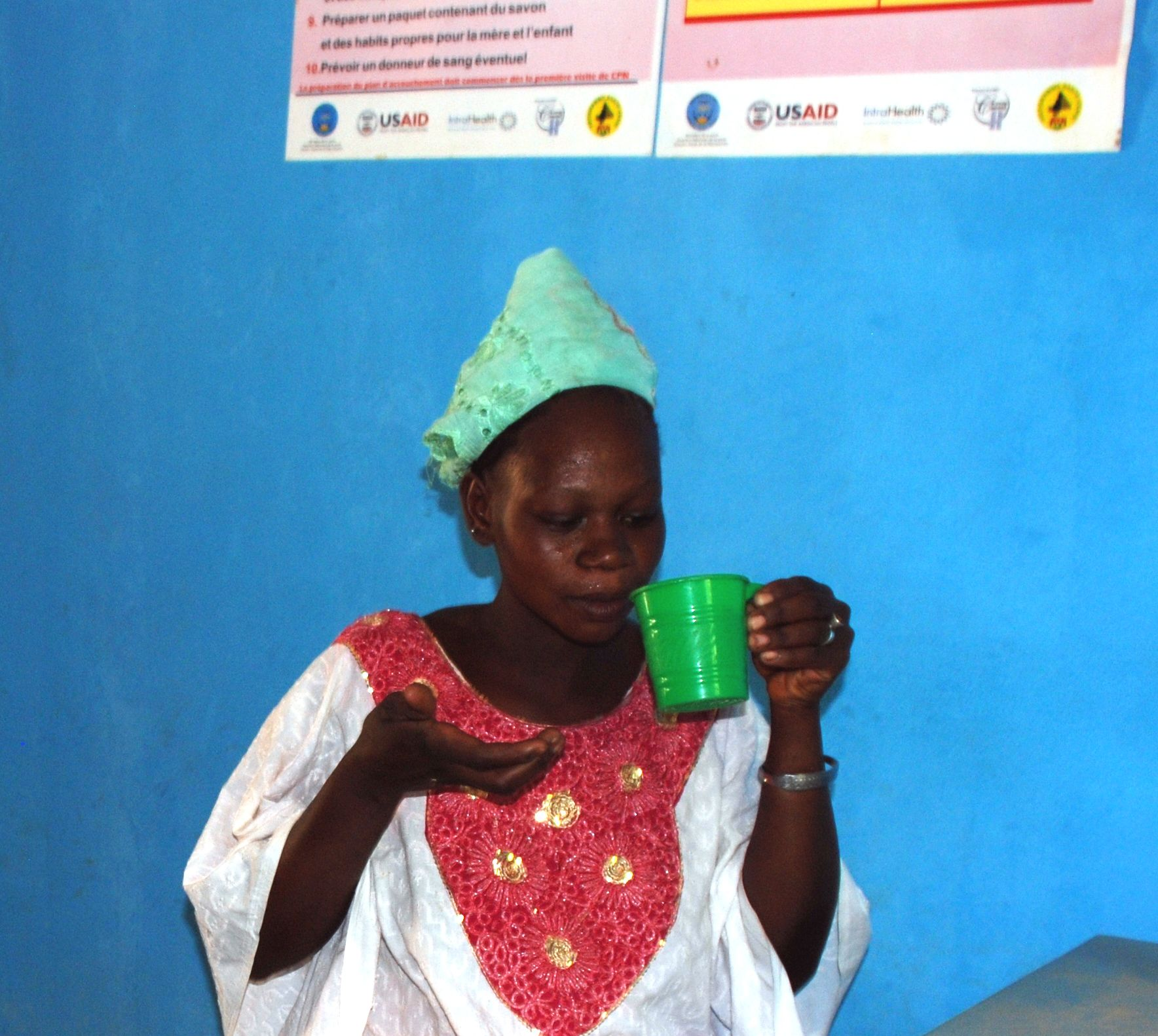 A pregnant woman takes tablets to protect herself from malaria.