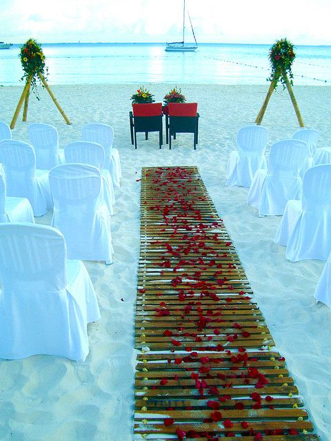I like this idea for the isle so our shoes don't sink into the sand...but with white wood foldable chairs and arch