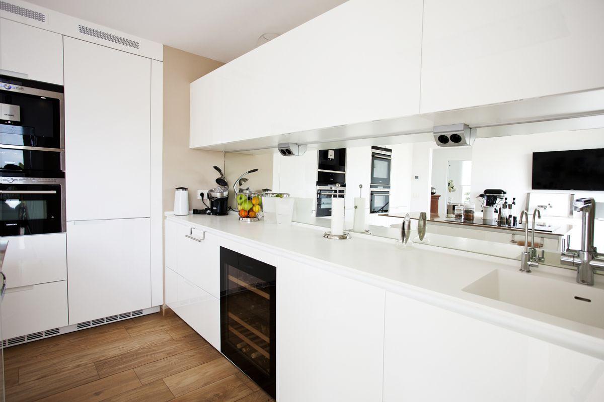 cocina en blanco con pared y encimera isla en color moka