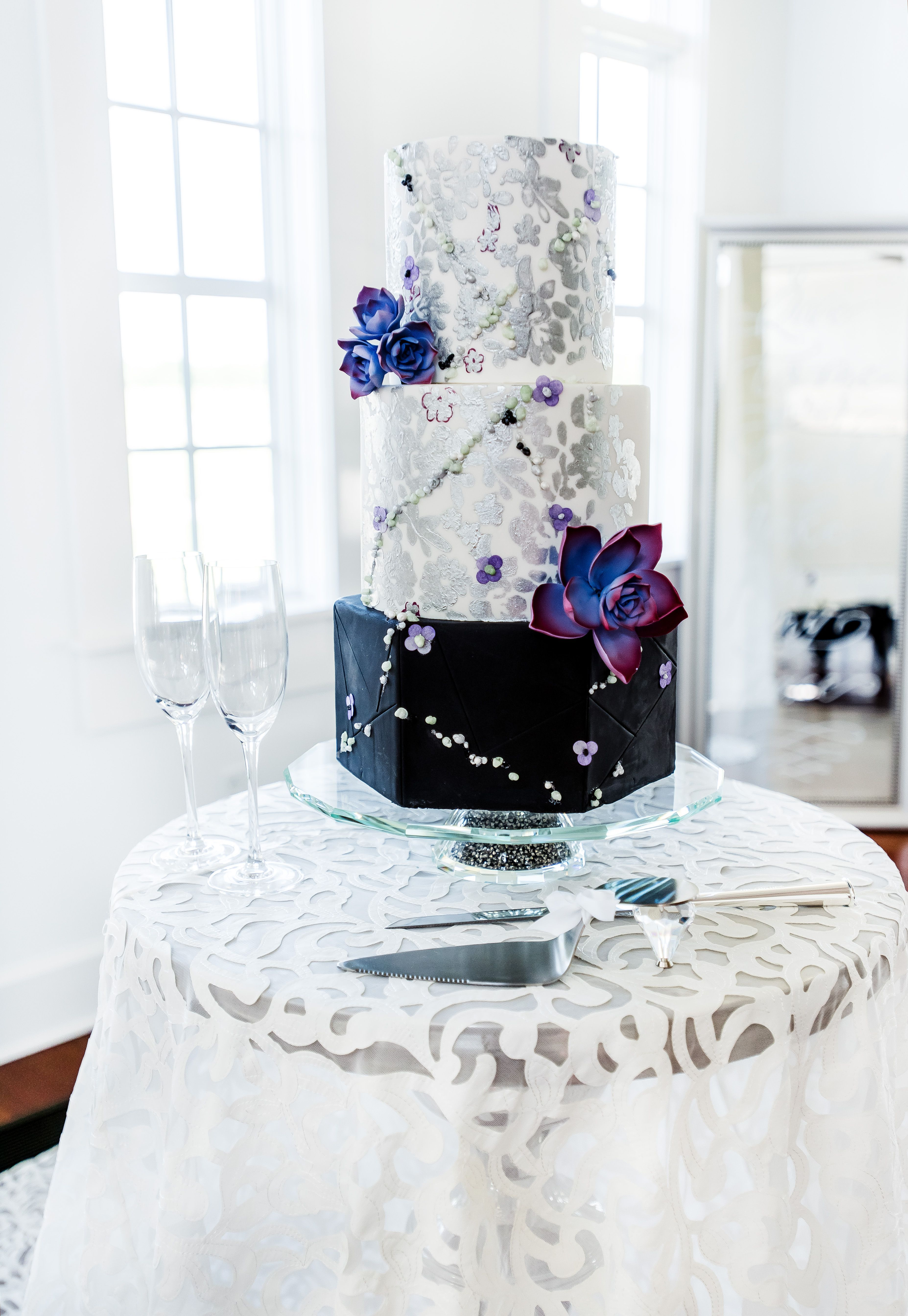 Black and white textured wedding cake with silver details on ...