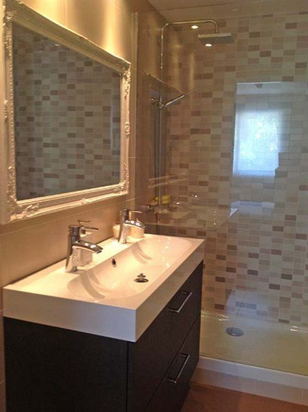 Renovated bathroom - love the modern double faucet sink and vanity, modern tiles, combined with a traditional, ornate frame around the mirror.