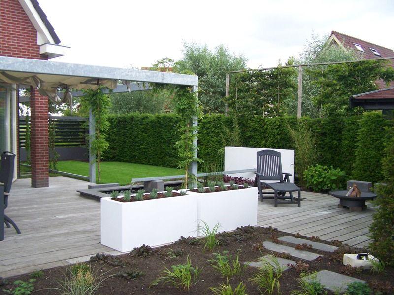 Strakke moderne tuin. witte bloembakken houten vlonder terras