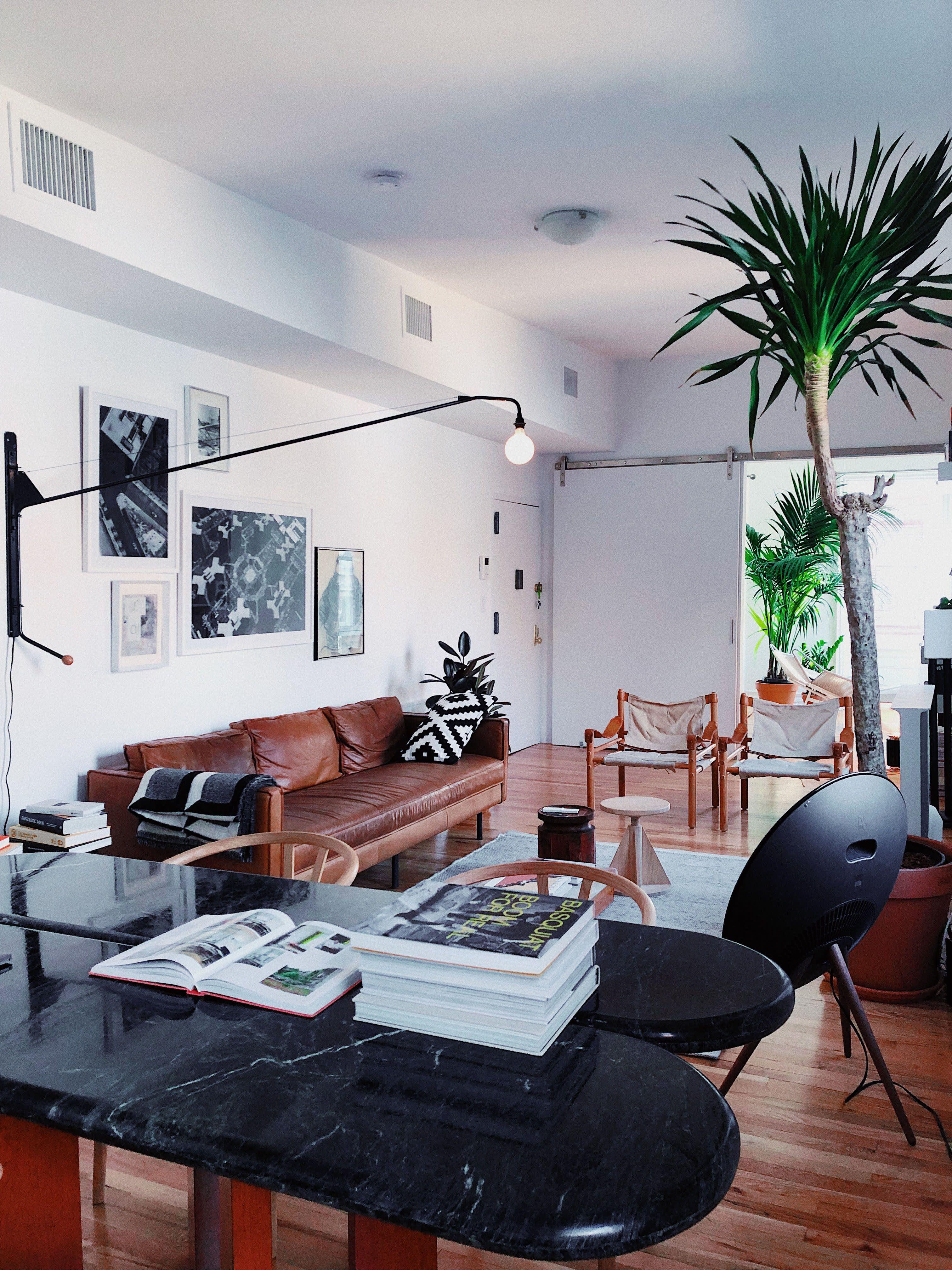 Behold Big Plants Beautiful Views And Bold Brick In This Sleek Nyc Loft Living Room Loft Small Living Room Decor Brick Wall Living Room