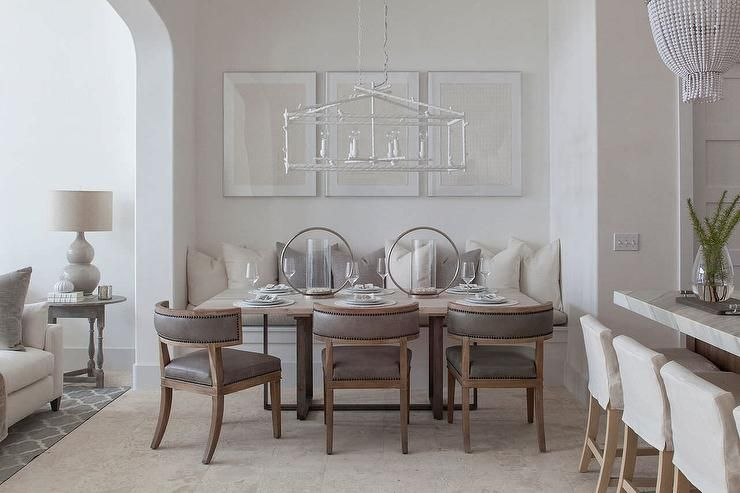Elegant Dining Room Boasts A Rectangular White Birdcage Chandelier Illuminating Trio Of Framed Art Pieces Standing Over Built In Bench Adorned