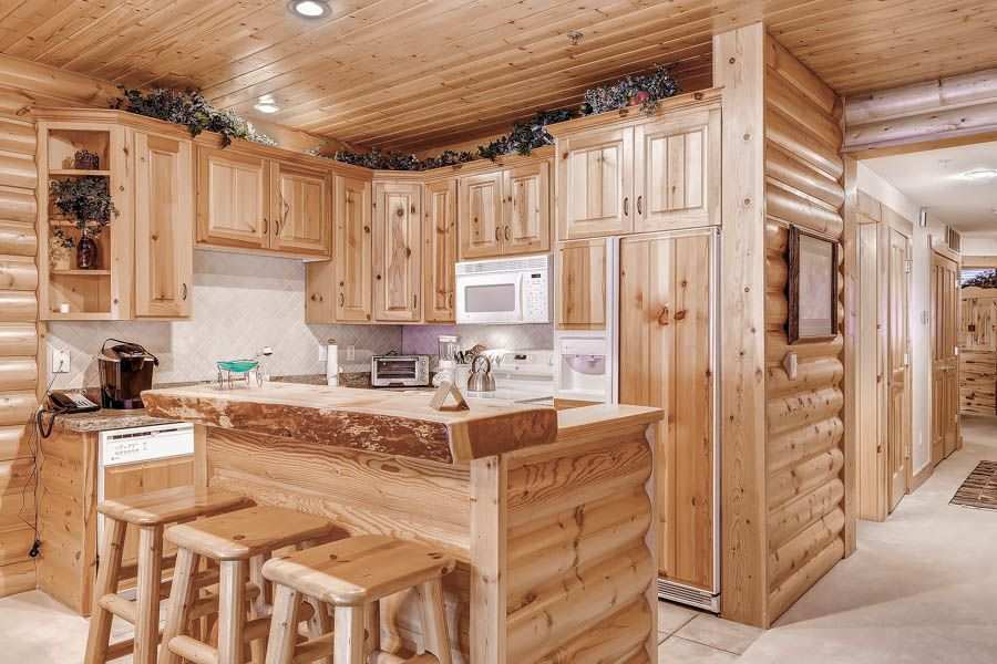 Upscale condominium with custom breakfast bar for 3; decorated in classic mountain style of interior log walls, knotty pine cabinets, & wood ceilings.