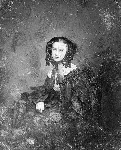 Daguerreotype Portrait of young unknown woman in black holding a photo of a man. Probably in Mourning for a Civil War Soldier.
