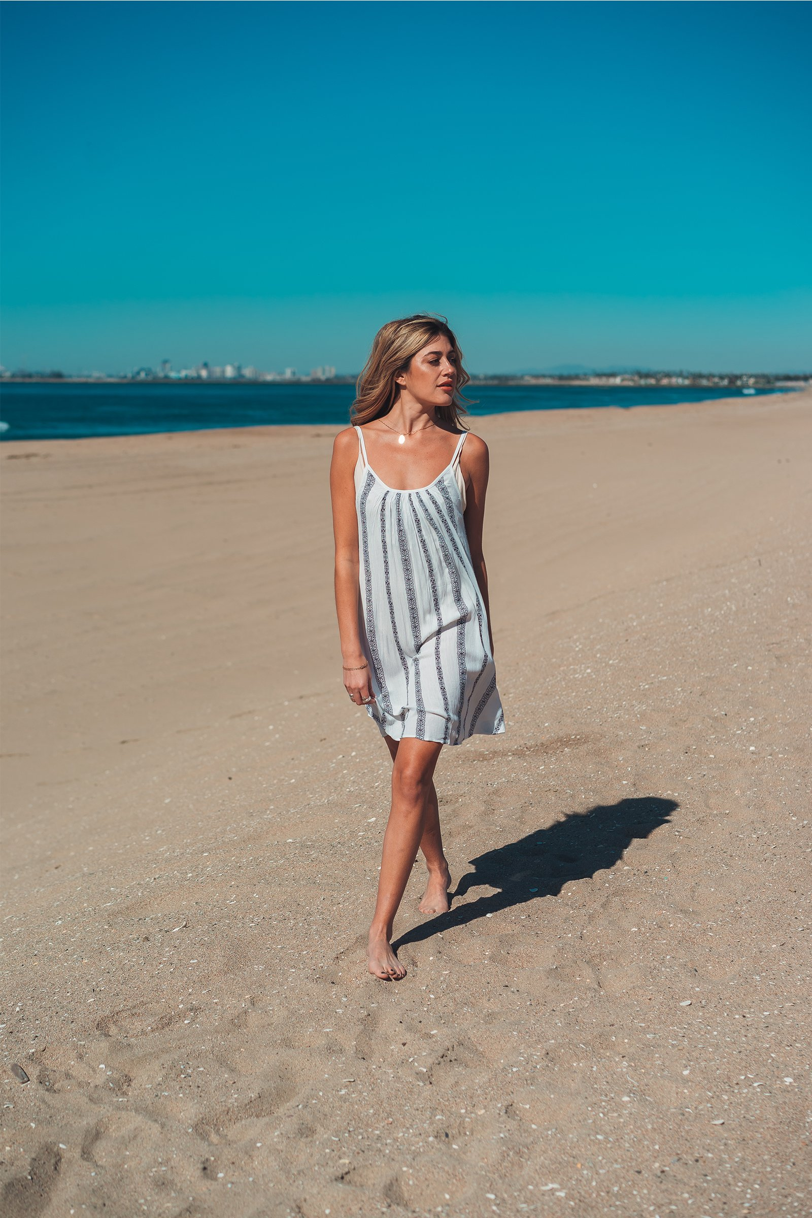 b940951e7ac2 A scoop back beach cover-up in a nautical stripe print with adjustable spaghetti  straps. Wear it in the day into the night! Model is 5 10 wearing size S. ...