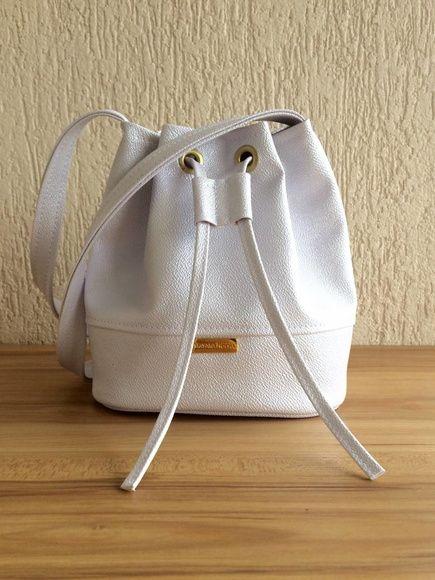 83c417e8d Bolsa modelo mini bucket em courvin perolado branco. Forro interno em  tecido cor nude.