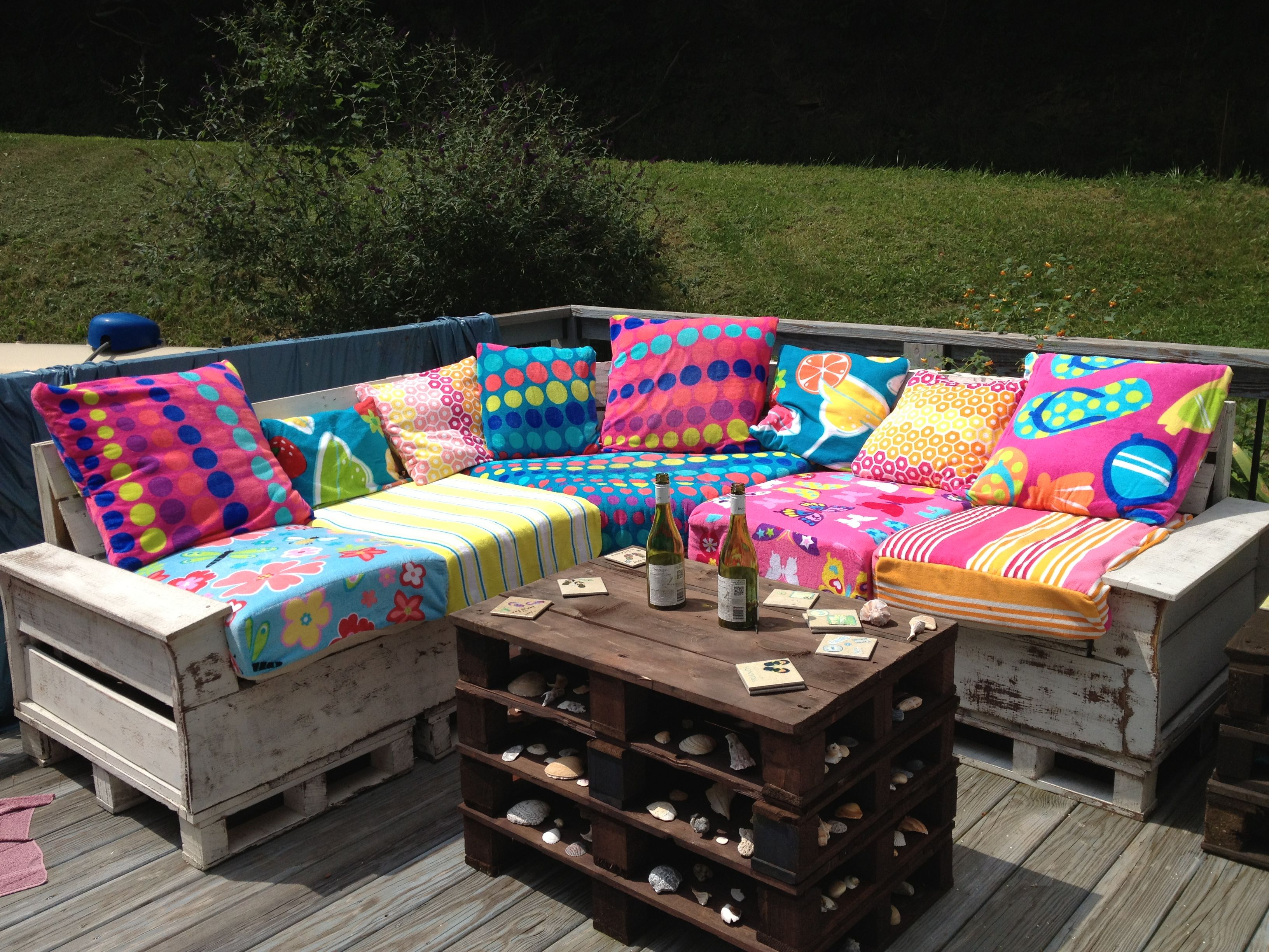 Made this pallet sectional for our back deck. Cushions are recycled from a old couch, and pillows just recovered with fun beach towel patterns! LOVE IT!