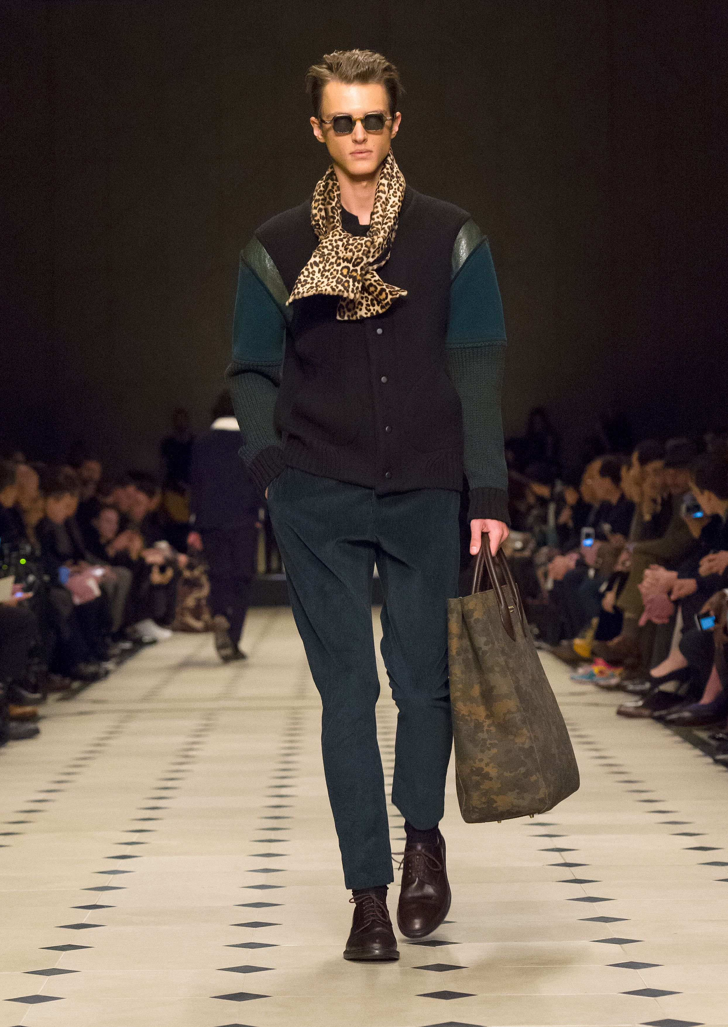 A black bomber jacket worn with corduroy trousers and The Carryall in camouflage print