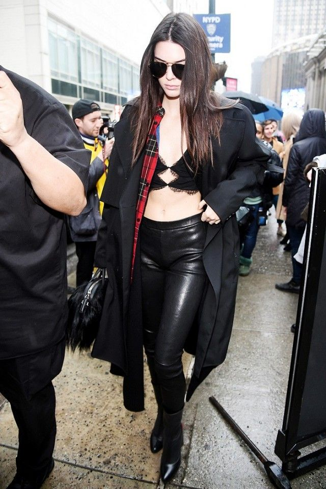 Kendall Jenner wears a lace bralette, plaid shirt, black coat, leather  leggings,