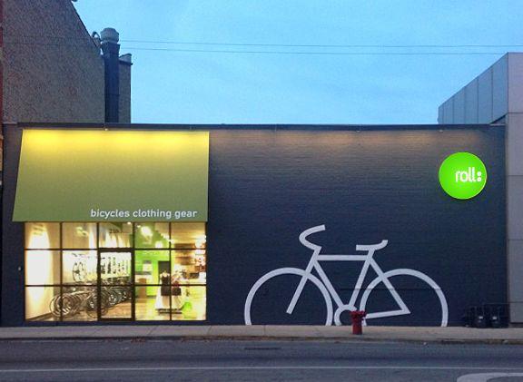 Fachada de tienda de bicicletas, tiene un toque moderno debido a los colores utilizados y da un mensaje claro de lo que vende. IV