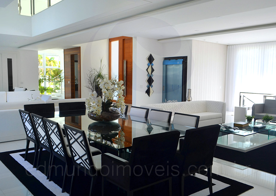 Na sala de jantar, a mesa com tampo espelhado acomoda até doze pessoas para as refeições mais formais. As cadeiras também contam com motivos geométricos em preto e branco, se integrando ao ambiente com leveza e suntuosidade.